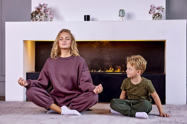 Europese vrouw met kind maakt thuis yoga-asana's