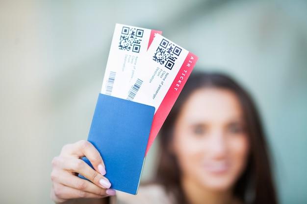 Europese vrouw met mooi bruin haar glimlachen terwijl paspoort en vliegtickets