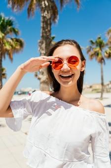 Europese vrouw op vakantie, staat op het strand in zonnebril, glimlacht vreugdevol en houdt haar hand over haar bril