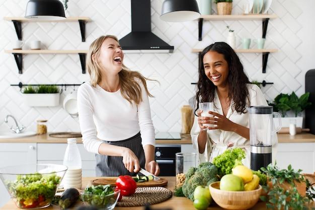 Europese vrouw snijdt een komkommer en afrikaanse vrouw drinkt melk, lachen ze