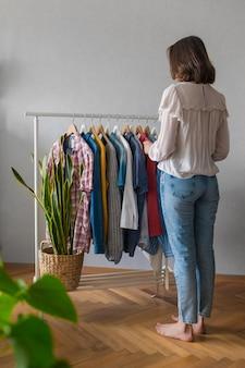Europese vrouw thuis in garderobe selecteert kleding voor een feest of verjaardagsfeestje en sorteert kleding