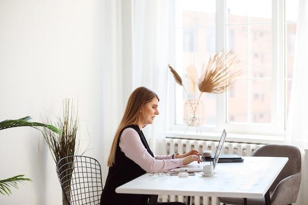 Europese vrouw werkt op haar laptop vanuit kantoor of thuis