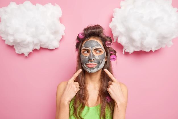 Europese vrouw wijst naar gezicht toont aan dat schoonheidsproduct op het gezicht van toepassing is, maakt krullend kapsel geconcentreerd opzij geïsoleerd over roze muur
