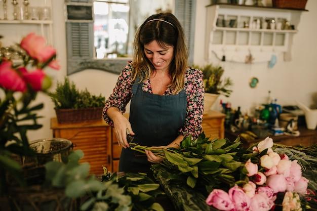Europese vrouwelijke bloemist die met een groen schort bloemstukken maakt