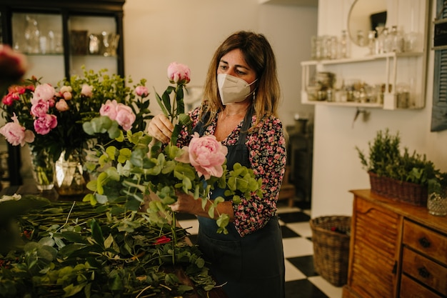 Europese vrouwelijke bloemist met een medisch gezichtsmasker dat bloemstukken maakt