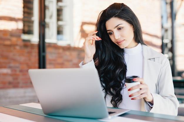 Europese vrouwelijke freelancer die aan ideeën voor haar nieuw project denkt dat met laptop computer werkt terwijl het zitten bij openluchtcafetaria