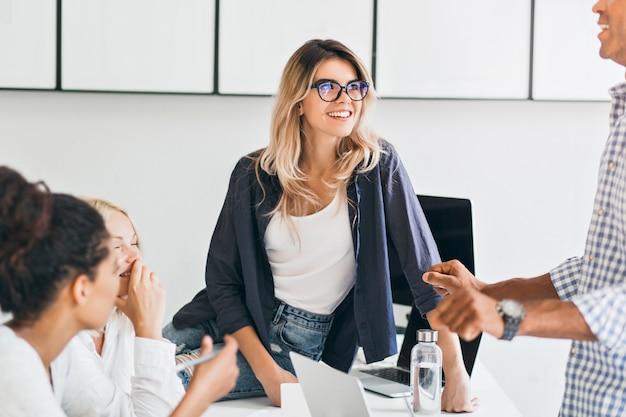 Europese vrouwelijke student in glazen koelen op tafel en universiteitsvriend luisteren in polshorloge. afrikaanse jonge vrouw praten met collega's in kantoor tijdens koffiepauze.