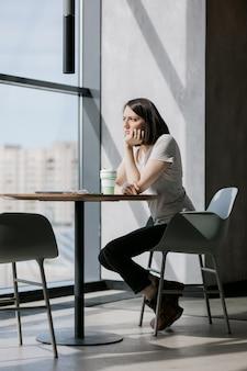Europese zakenvrouw in glazen koffie drinken en praten aan de telefoon
