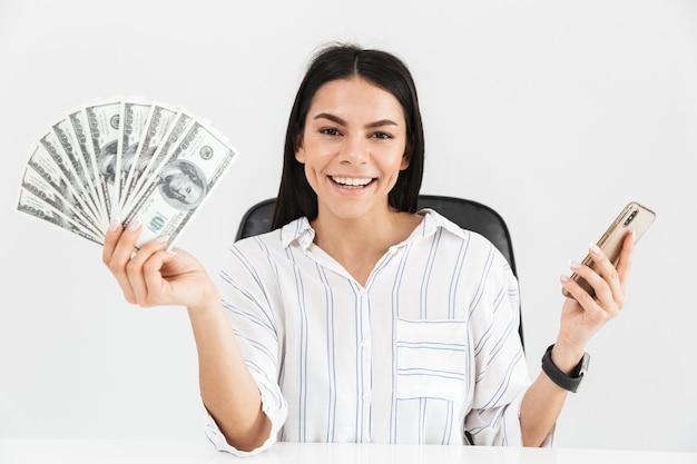Europese zakenvrouw smartphone en ventilator met geld dollar biljetten zittend in een fauteuil in kantoor geïsoleerd over witte muur te houden