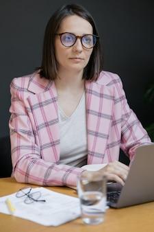 Europese zelfverzekerde zakenvrouw in een roze jas en met een laptop in haar kantoor aan het werk