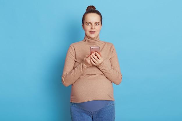 Europese zwangere telefoon houden en direct kijken naar camera geïsoleerd over blauwe muur.