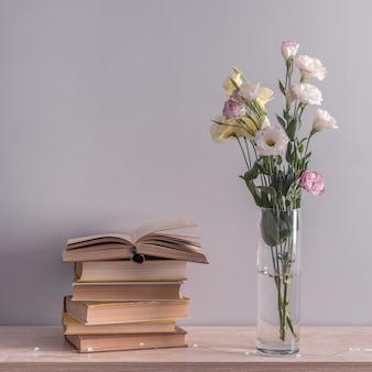 Eustoma bloeit boeket in een vaas, stapel oude vintage boeken en guirlande lichten. lezen en ontspannen concept.