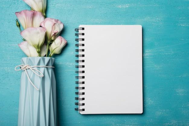 Eustoma bloeit vaas met spiraalvormig leeg notitieboekje op blauwe achtergrond