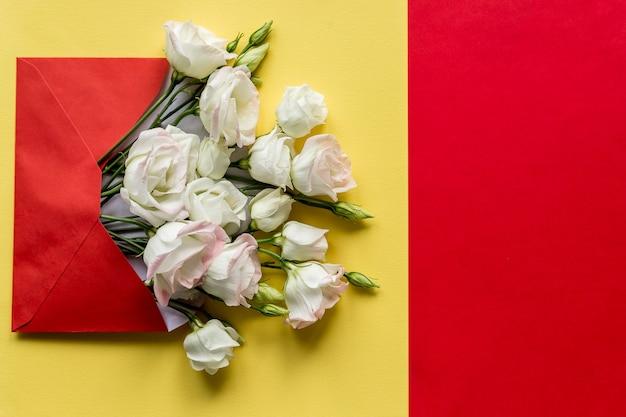 Eustoma bloemen met envelop op kleurrijke achtergrond. geopende envelop met witte bloemen arrangementen. feestelijke groet concept. heldere verse compositie