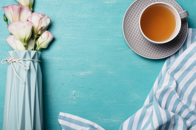 Eustoma bloemenvaas met kopje thee en servet op blauwe achtergrond