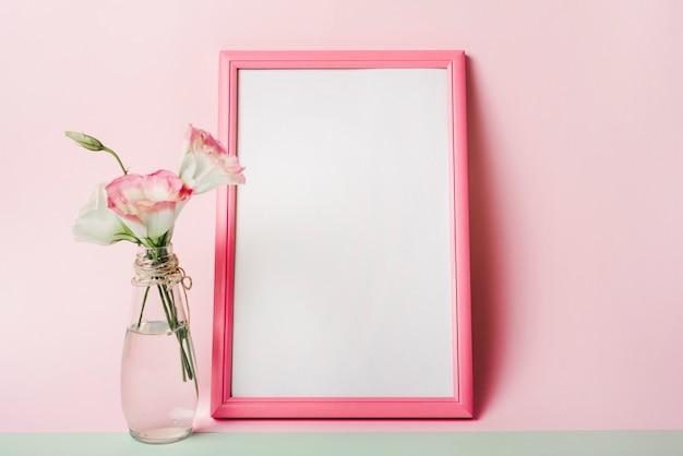 Eustomabloemen in vaas dichtbij het lege witte kader met grens tegen roze achtergrond