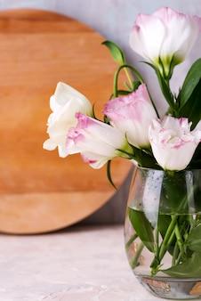 Eustomabloemen in vaas op lijst dichtbij houten plaat en steenmuur, close-up.