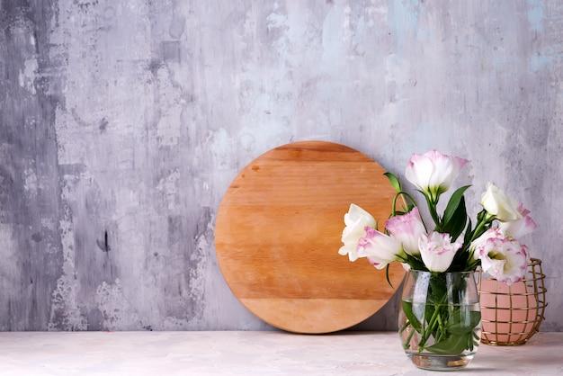 Eustomabloemen in vaas op lijst dichtbij steenmuur. spatie voor ansichtkaarten
