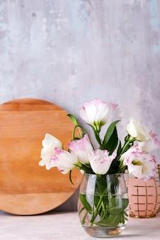 Eustomabloemen in vaas op lijst dichtbij steenmuur.