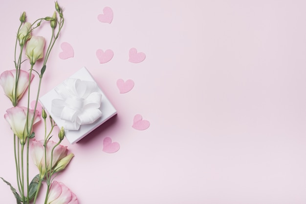 Eustomabloemen met roze harten en witte giftdoos met lint op gekleurde achtergrond