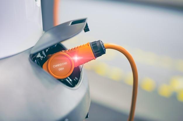 Ev-auto of elektrische auto bij laadstation met de stroomkabel aangesloten, modern milieuvriendelijk energie-rijdend voertuig