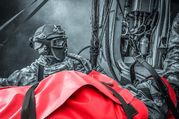 Evacuatie van een gewonde soldaat per helikopter. het slachtoffer ligt op een brancard. het concept van militaire conflicten. van hoge kwaliteit