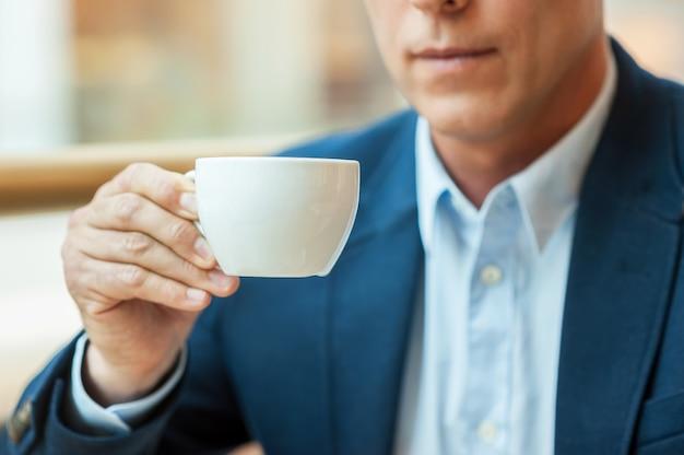 Even pauze met verse koffie. vrolijke volwassen man in formalwear die koffie drinkt en glimlacht terwijl hij in de coffeeshop zit