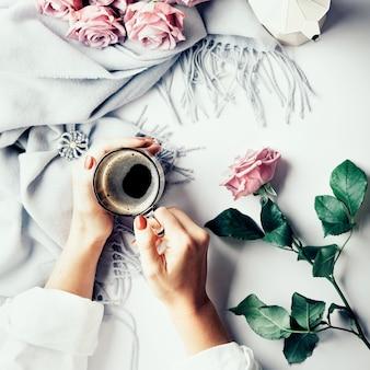 Even pauze: vrouwelijke handen met kopje koffie. flatlay met wollen sjaal en roze rozen. overzicht.