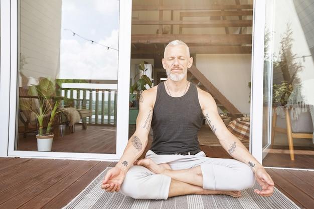 Evenwicht in het leven ontspannen blanke man van middelbare leeftijd zittend in lotushouding op het zonnige terras van zijn
