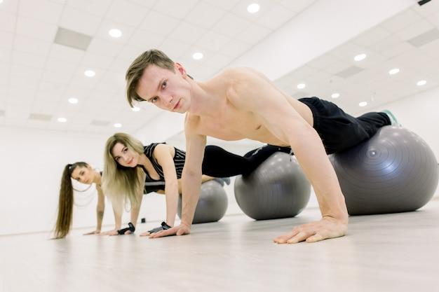 Evenwicht, krachtconcept. sportieve man en twee vrouwen doen handstand met benen op fit bal. mensen in sportkleding training op fitball in de sportschool. sport, fitnesstraining