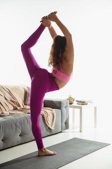 Evenwicht. mooie jonge vrouw die binnenshuis uitwerkt, yogaoefening op grijze mat thuis doet. onherkenbaar kaukasisch model oefenen. concept van een gezonde levensstijl, mentaal, mindfullness, balans.