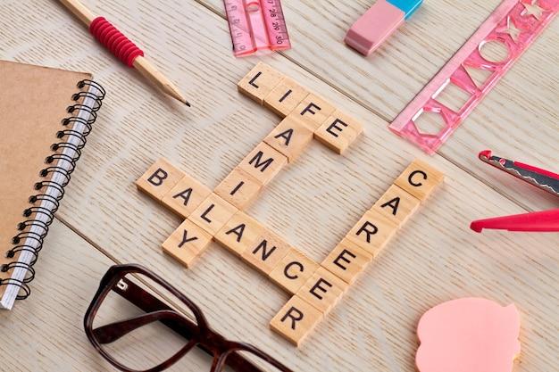 Evenwicht tussen carrière en gezin. kruiswoordraadsel gemaakt van houten blokken met letters. kladblok met pen en zonnebril op het bureau.