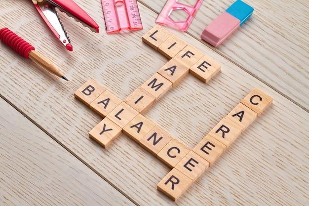 Evenwicht tussen loopbaan en gezinsleven. schaar met liniaal en potlood op het houten bureau.
