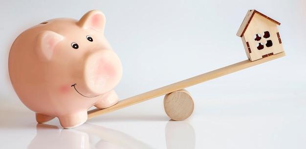 Evenwicht tussen roze varken en wodden huis. concept geld besparen op witte muur