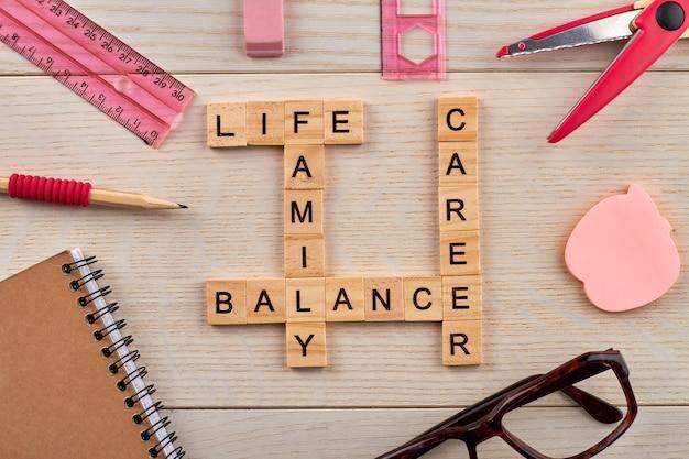 Evenwicht tussen werk en privé. bovenaanzicht van kruiswoordraadsel met carrière- en familiewoorden. briefpapier en zonnebril op de houten tafel.