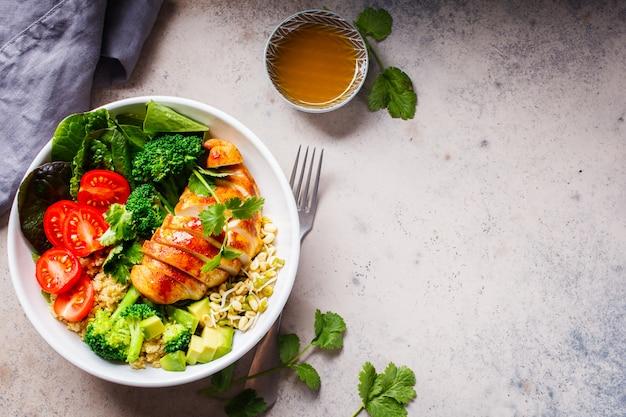 Evenwichtig voedselconcept. kip, broccoli en quinoa salade in witte kom, grijze achtergrond, bovenaanzicht.