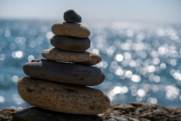 Evenwichtige kiezelpiramide op het strand op een zonnige dag abstracte zee bokeh op de achtergrond selectief