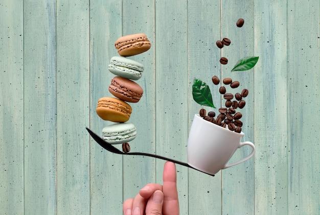 Evenwichtige kopje koffie en macarons op een vinger
