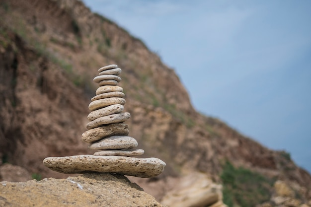 Evenwichtige piramide van stenen op een grote steen op de kust