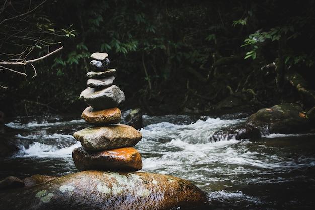 Evenwichtige stenen pyramide op de oever van water val van bergmeer. blauwe bergen in waterspiegelspiegel. slechte lichtomstandigheden.