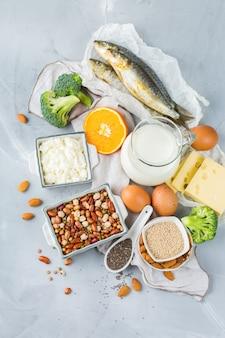 Evenwichtige voeding, gezond eten concept. assortiment van voedselbronnen rijk aan calcium, bonen, zuivelproducten, sardines, broccoli, chiazaden, amandelen op een keukentafel
