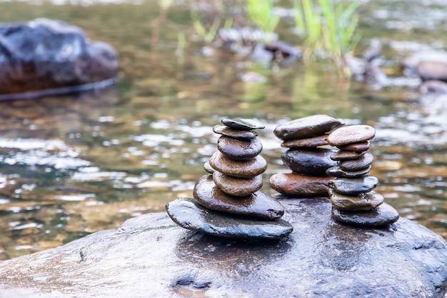 Evenwichtige zen-rotsstapels in een kreek, weergave van een kreek met gestapelde stenen op een rots