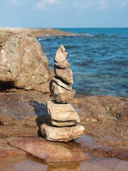 Evenwichtige zenstenen op het strand met blauwe lucht en de zee.