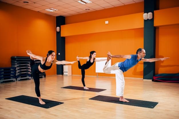 Evenwichtsoefening, vrouwelijke yogagroep in actie, training met instructeur, trainen in de sportschool. yogi binnen