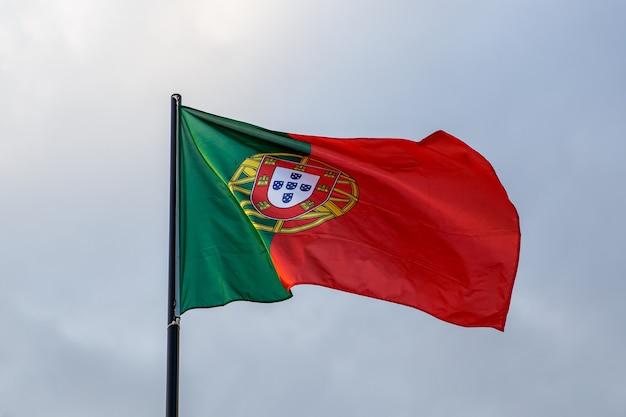 Evoluerende portugese vlag, wolken op blauwe hemel