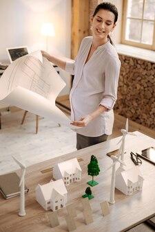 Exact model. bovenaanzicht van zelfverzekerde aangename zwangere ontwerper glimlachend terwijl blauwdruk vasthoudt en model op tafel kijkt