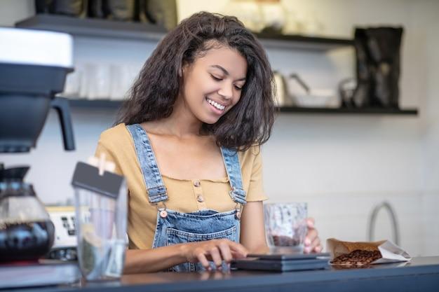 Exacte maat. attente lachende jonge volwassen vrouw in denim overall nauwkeurig koffiebonen meten achter de toonbank in café