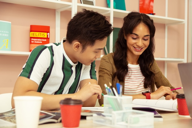 Examen voorbereiding. vrij langharig meisje dat een glimlach op haar gezicht houdt terwijl ze naar haar schrijfboek kijkt