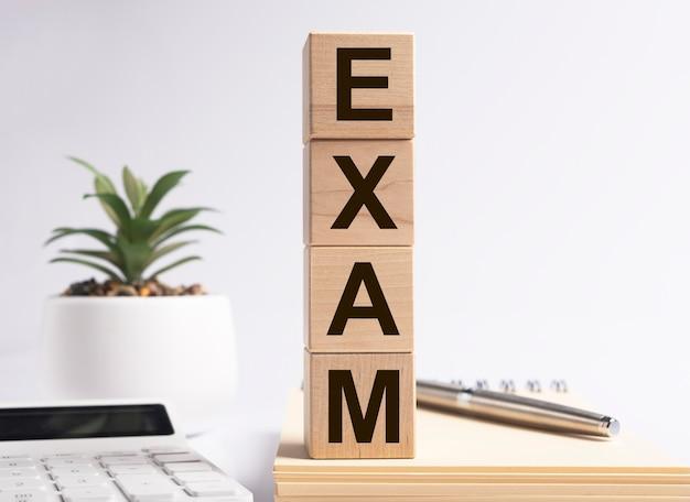 Examenwoord op houten kubussen. economie of wiskunde.