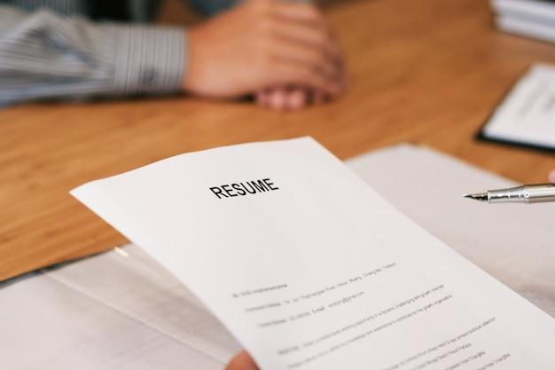Examinator lezen van een cv tijdens sollicitatiegesprek op kantoor conc zaken en personeel conc
